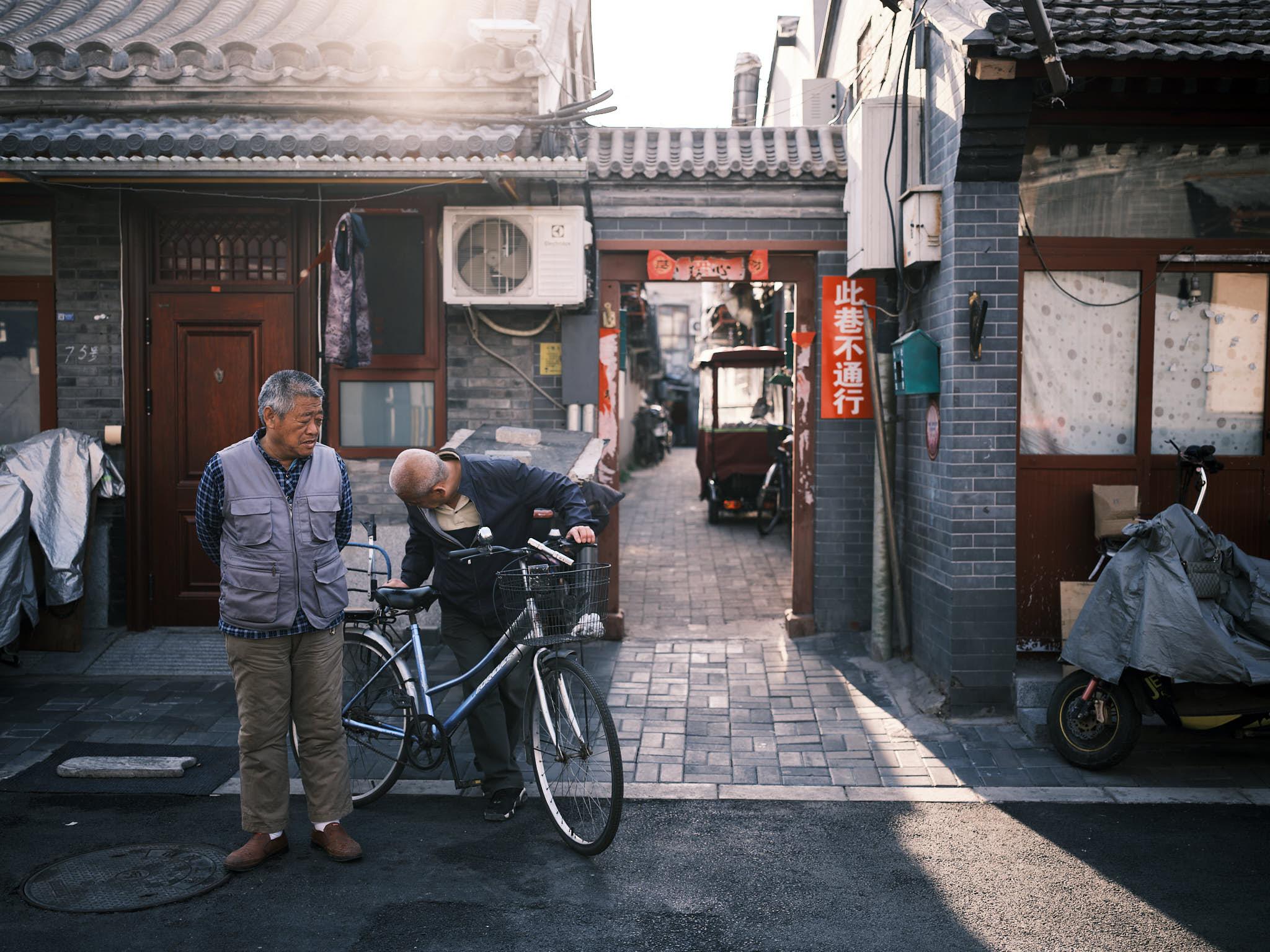 Old men fixing a bike in Qianmen Hutong Beijing