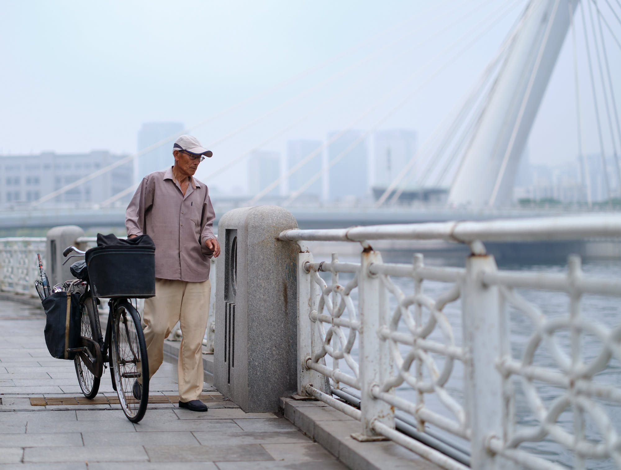 Older man walking his bicycle along the river in Tianjin, China